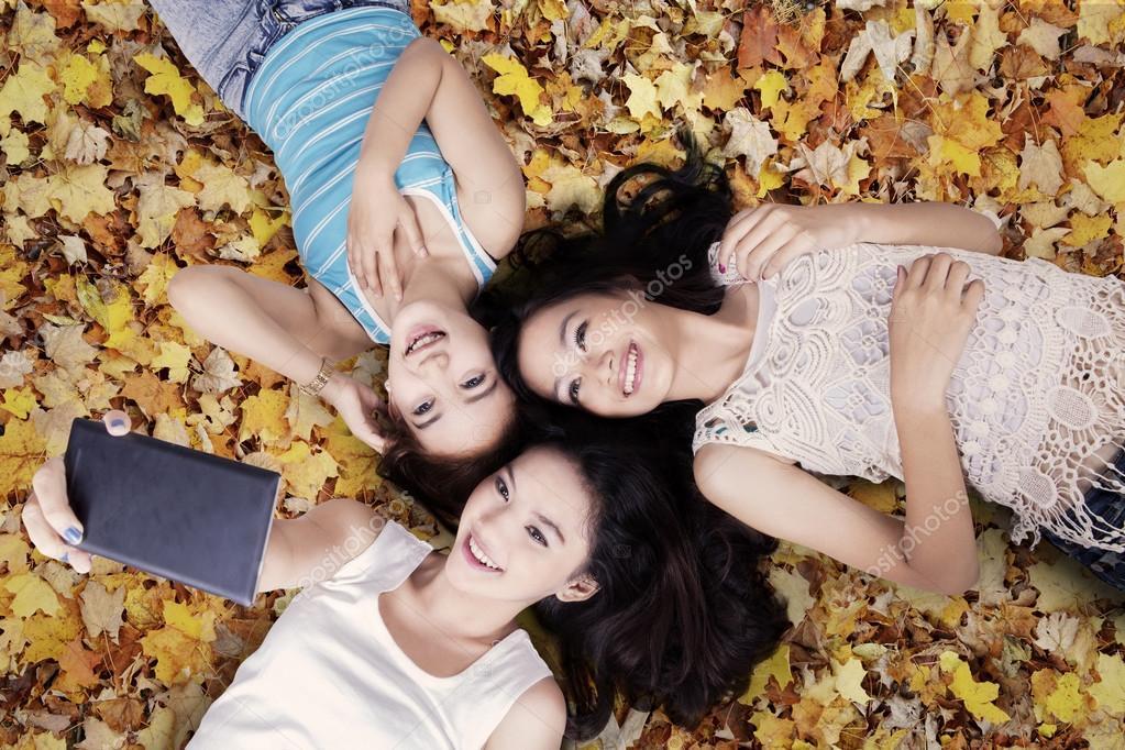 Girls taking photos on autumn leaves