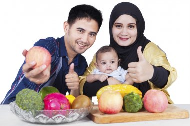 Healthy family with fruits and thumbs-up