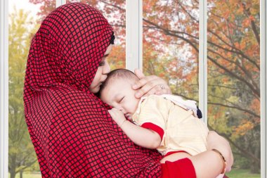 Muslim mother lull her baby at home