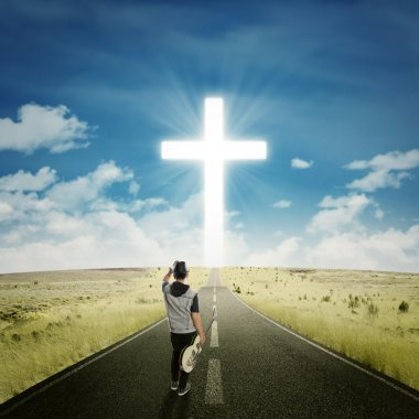 Singer with guitar walks to the cross