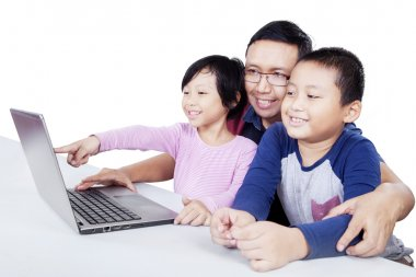 Kids using laptop on the table with their father
