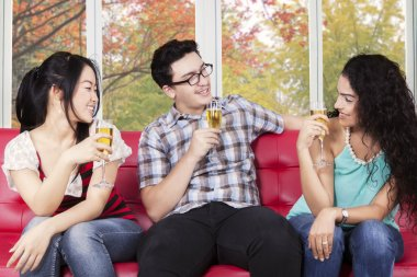 Teenagers enjoy champagne at home