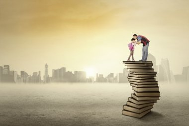 Young father kissing his daughter above a pile of books before going to school, shot outdoors stock vector