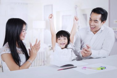 Cheerful kid getting applause from her parents
