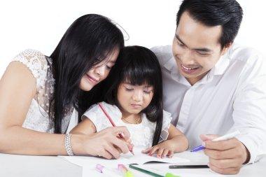 Hispanic parents teach their child to write