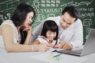 Two parents teach their child in the class