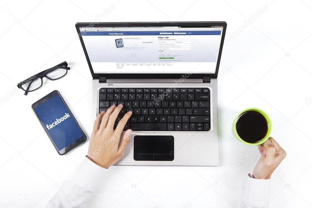 Worker holds coffee while opening facebook site
