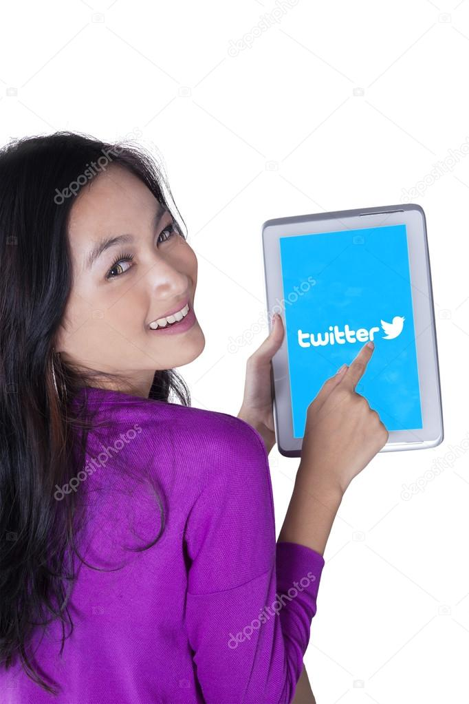 Girl holding a tablet with twitter logo