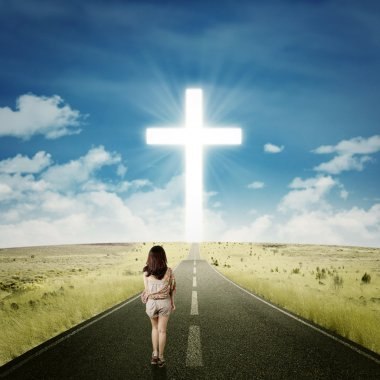Casual girl walking toward a cross