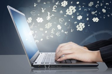 Woman hands typing on laptop with currency symbols