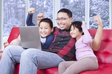 Joyful children and father with laptop