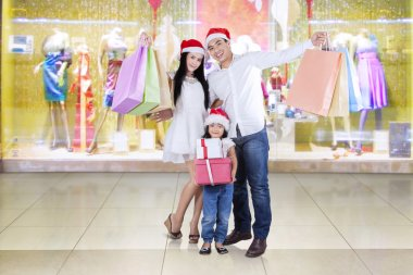 Joyful family with christmas gifts in shopping center
