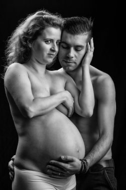 pregnant woman with husband holding her belly
