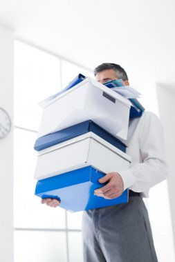 Frustrated businessman carrying boxes