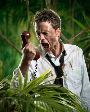 Furious businessman on the phone lost in jungle