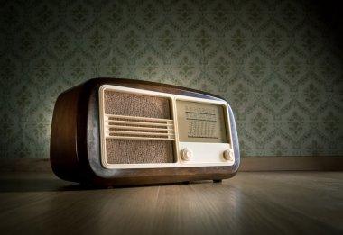 Old vintage radio on hardwood floor with retro wallpaper on background. stock vector