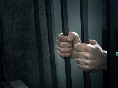 Man in jail hands close-up