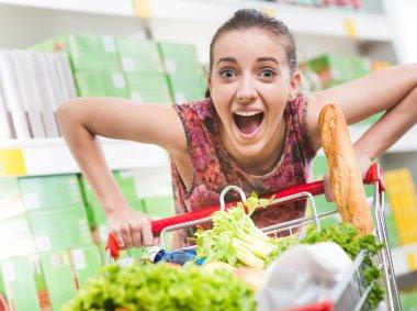 Woman mouth open pushing shopping cart