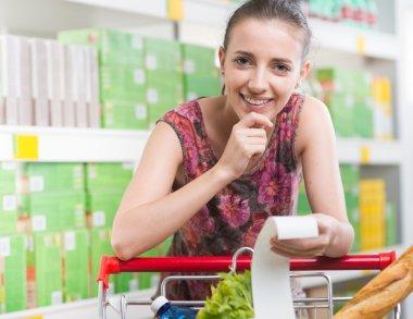 Woman checking long receipt at supermarket
