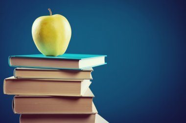 Books and yellow apple