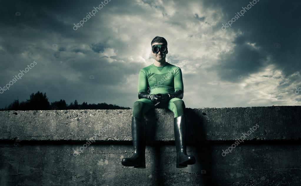 superhero sitting on a concrete wall