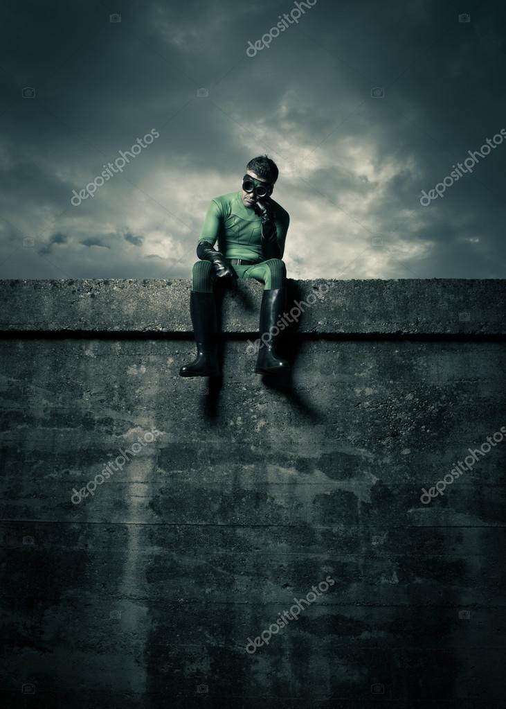 superhero sitting on concrete wall