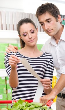 Couple checking supermarket receipt