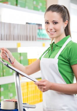 Female sales clerk holding clipboard