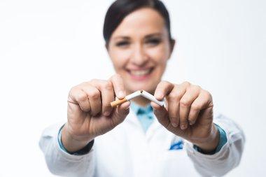 Female doctor breaking cigarette
