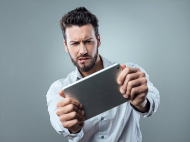 Confused man watching his tablet