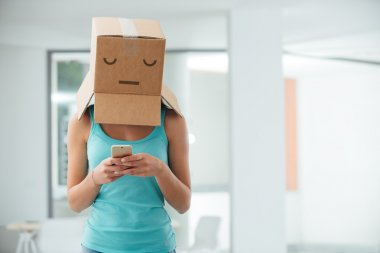 girl with a box on her head texting
