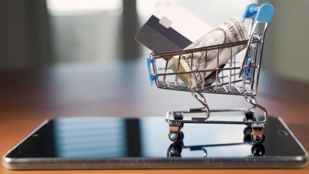 Malý nákupní košík s americkými dolary a kreditní kartou.