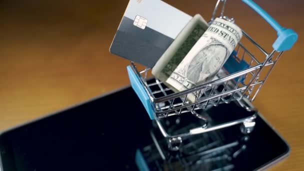 Small shopping cart with US Dollars and a credit card on it.