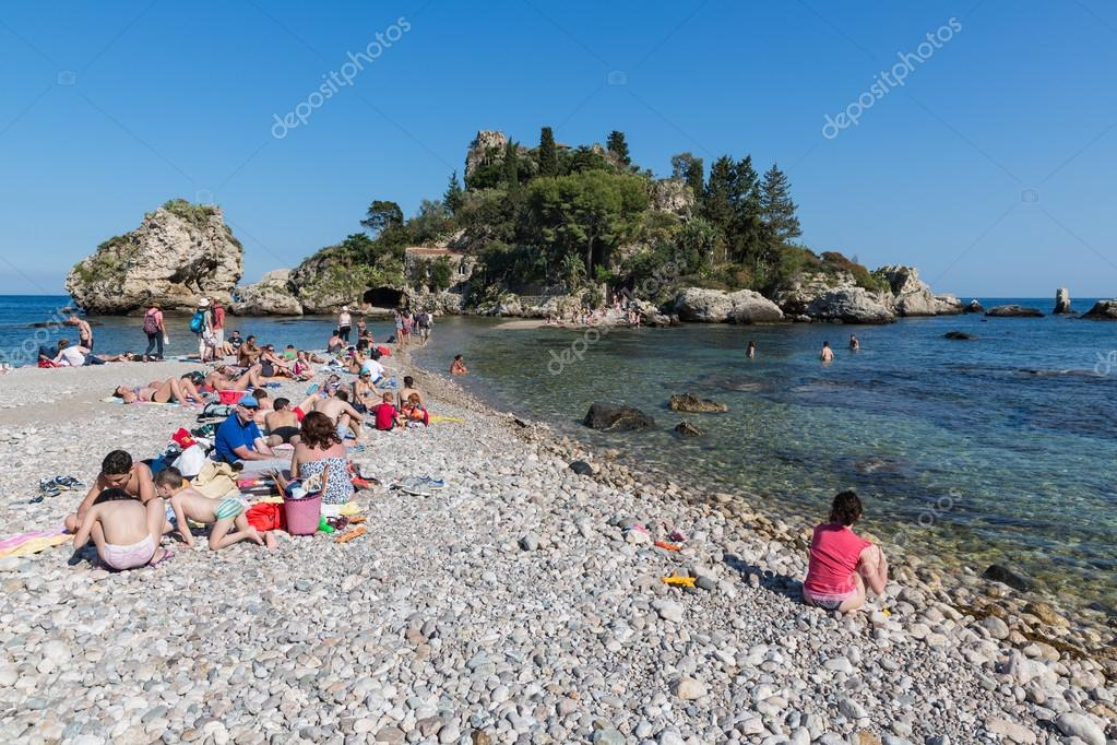 tourists relaxing at the beach of taormina at sicily italy stock