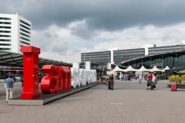 Airport square with Amsterdam logo and unknown travellers