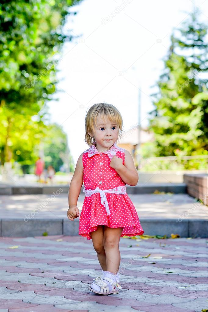 little girl walks in the park in the summer