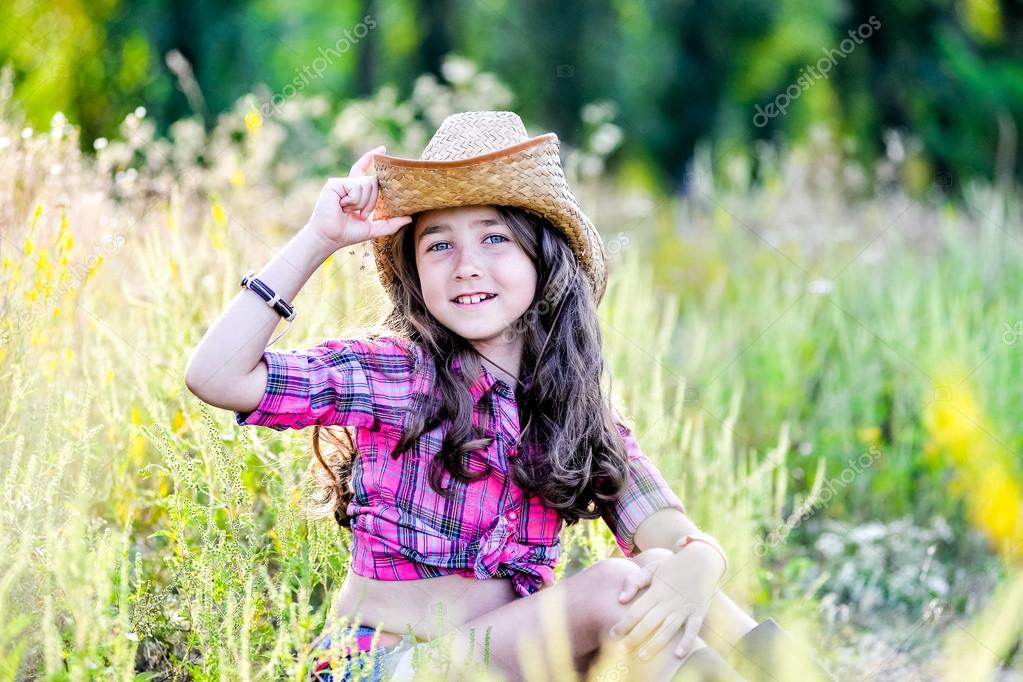 Happy baby girl with toy gun and cowboy hat enjoying nature. American  Cowgirl. lovely smiling toddler portrait. 192d226b7480