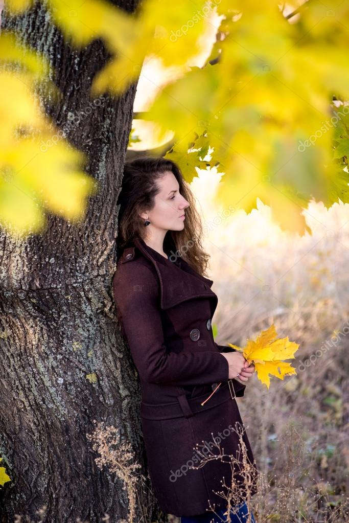 young woman in autumn park standing near tree