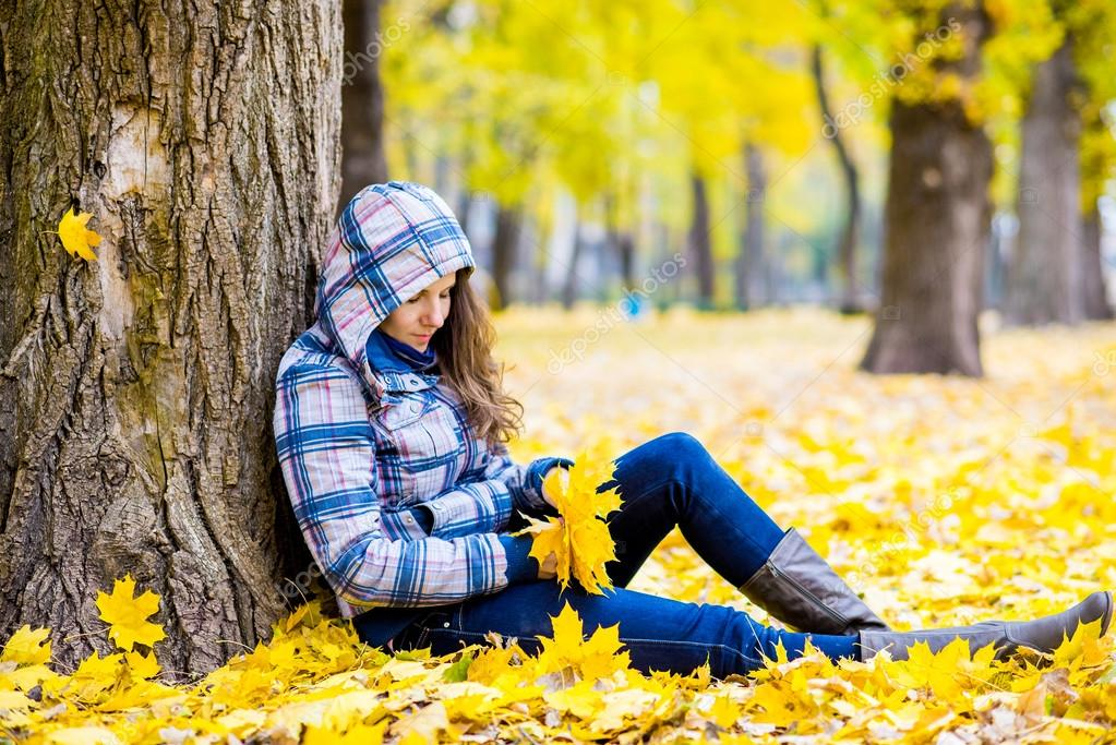young woman in autumn park sitting near tree