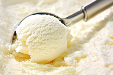 Vanilla ice cream scoop, scooped out of container with utensil