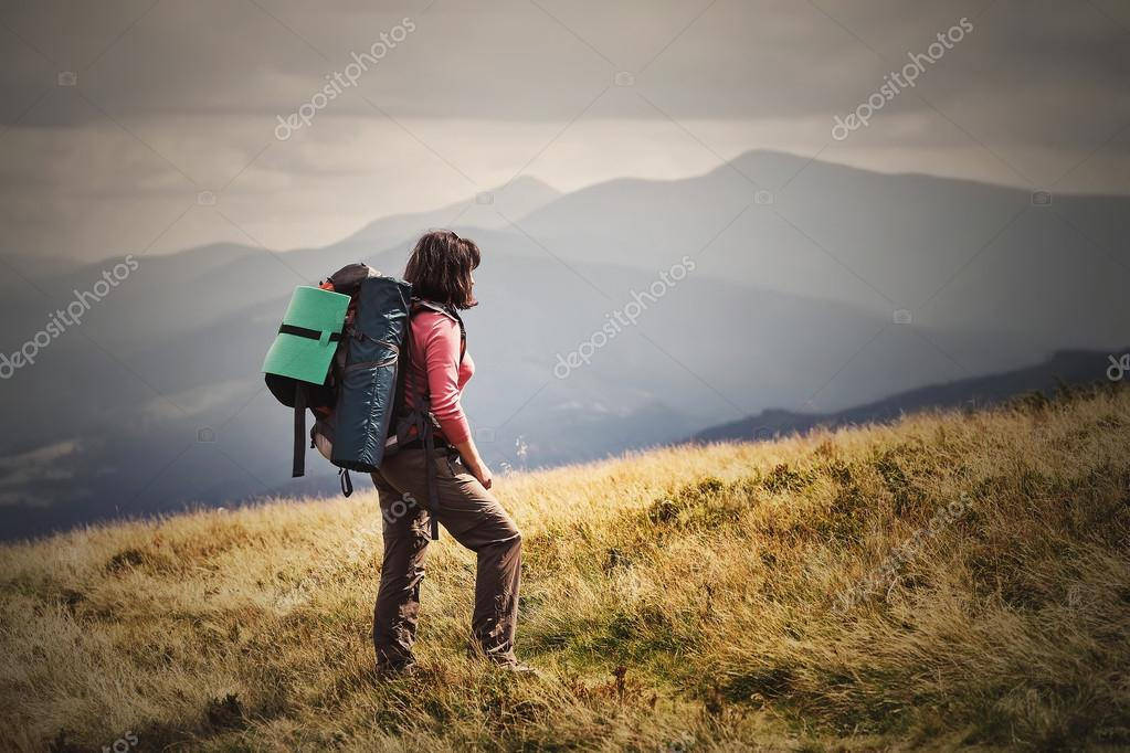 Young woman hiking on mountains with backpack Travel Lifestyle a
