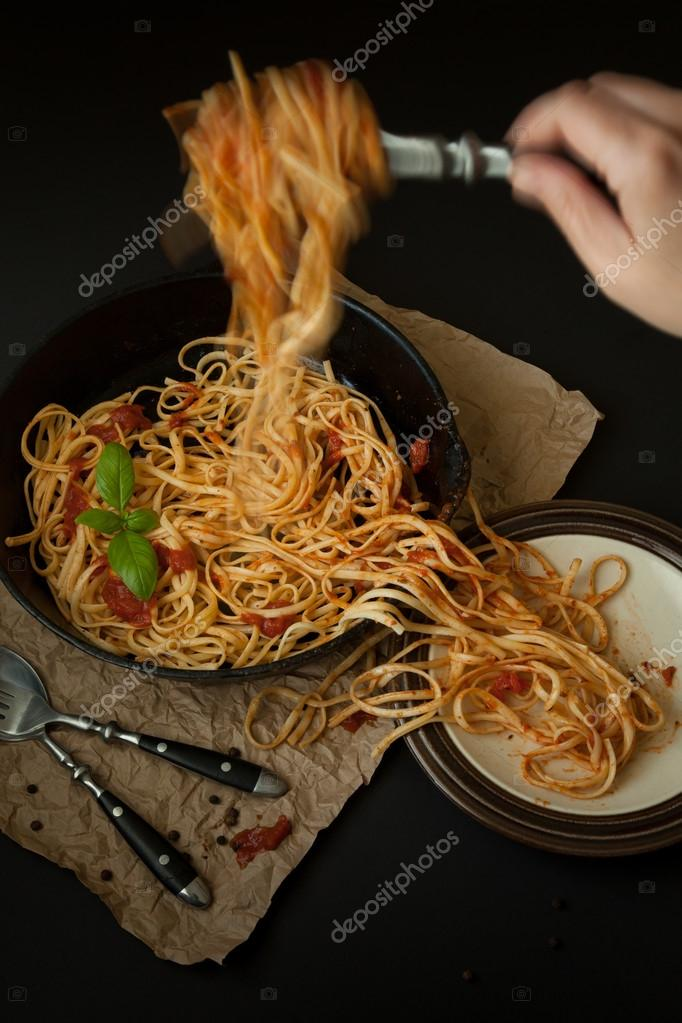 Linguine with Basil and Red Sauce in Cast Iron Pan Being Served