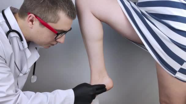 Ortopedický chirurg zkoumá ženskou nohu. Bolest nohou, vymknutí šlach, zánět, ploché nohy, bursitida, fasciitida. Myšlenka léčby onemocnění nohou. Doktor bude hmatat, aby zjistil zdroj bolesti.