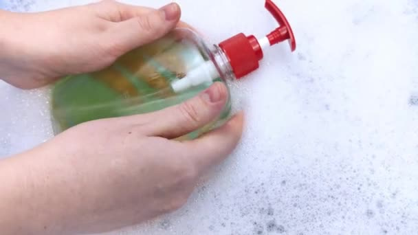 Bottles of detergents float in the foam. The concept of the dangers of household chemicals. Sodium laureate, parabens, sulfates and other chemical compounds in the foam. Liquid soap in a yellow jar