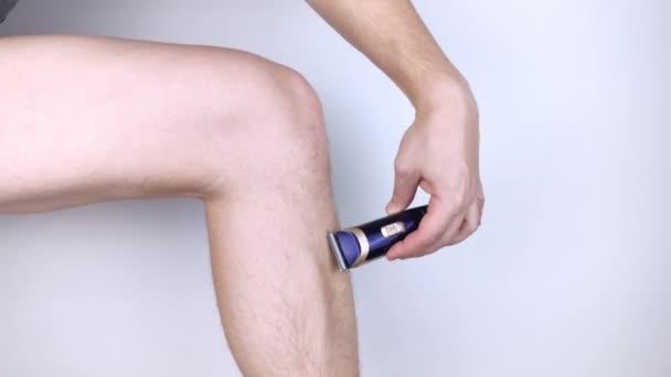 Muž na bílém pozadí si holí nohy. Chlupaté nohy a starat se o ně. Pojem rovnosti pohlaví. Detailní záběr s pěnou, břitvou a oholenými vlasy na hladké noze.