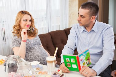 Picture of a pregnant woman showing a lollipop to her husband, sitting at the kitchen table stock vector