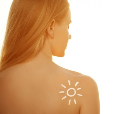 Suntan lotion cream. Woman care skin. Girl applying sunscreen so