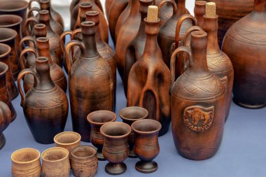 31.08.2019 Polotsk Belarus Amphorae, bottles and other hand-made clay items on the table. Wine and oil containers made of dark brown ceramic. Belarusian ceramics.