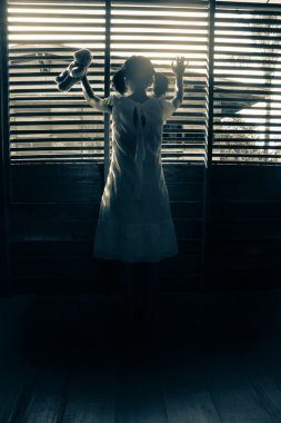 Mysterious girl in white dress standing in abandon house holding hand on the window