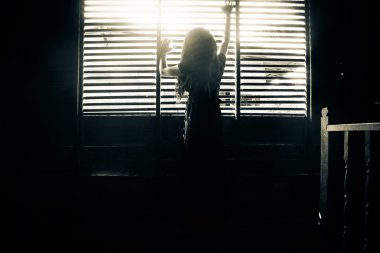 Mysterious girl in black dress standing in abandon house holding hand on the window